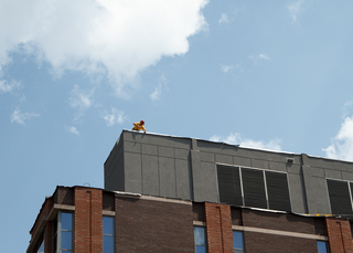 A construction worker installs roof liner to the top of the Center for Science and Technology building as crews replace its roof. This project is expected to be finished before fall classes begin. Photo taken Aug. 1, 2017