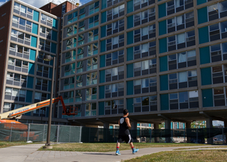 A student passes by DellPlain Hall, where upgrades to the building's dorms will be completed before the fall semester starts. Photo taken Aug. 8, 2017